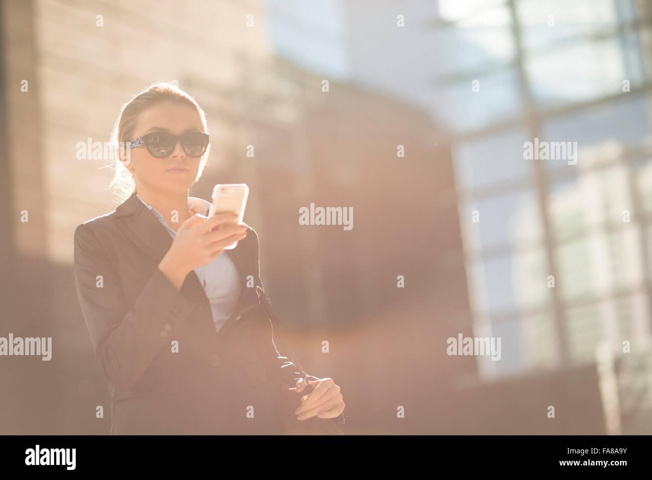 Ciudad joven empresaria leer texto smartphone fuera de oficina Foto de stock