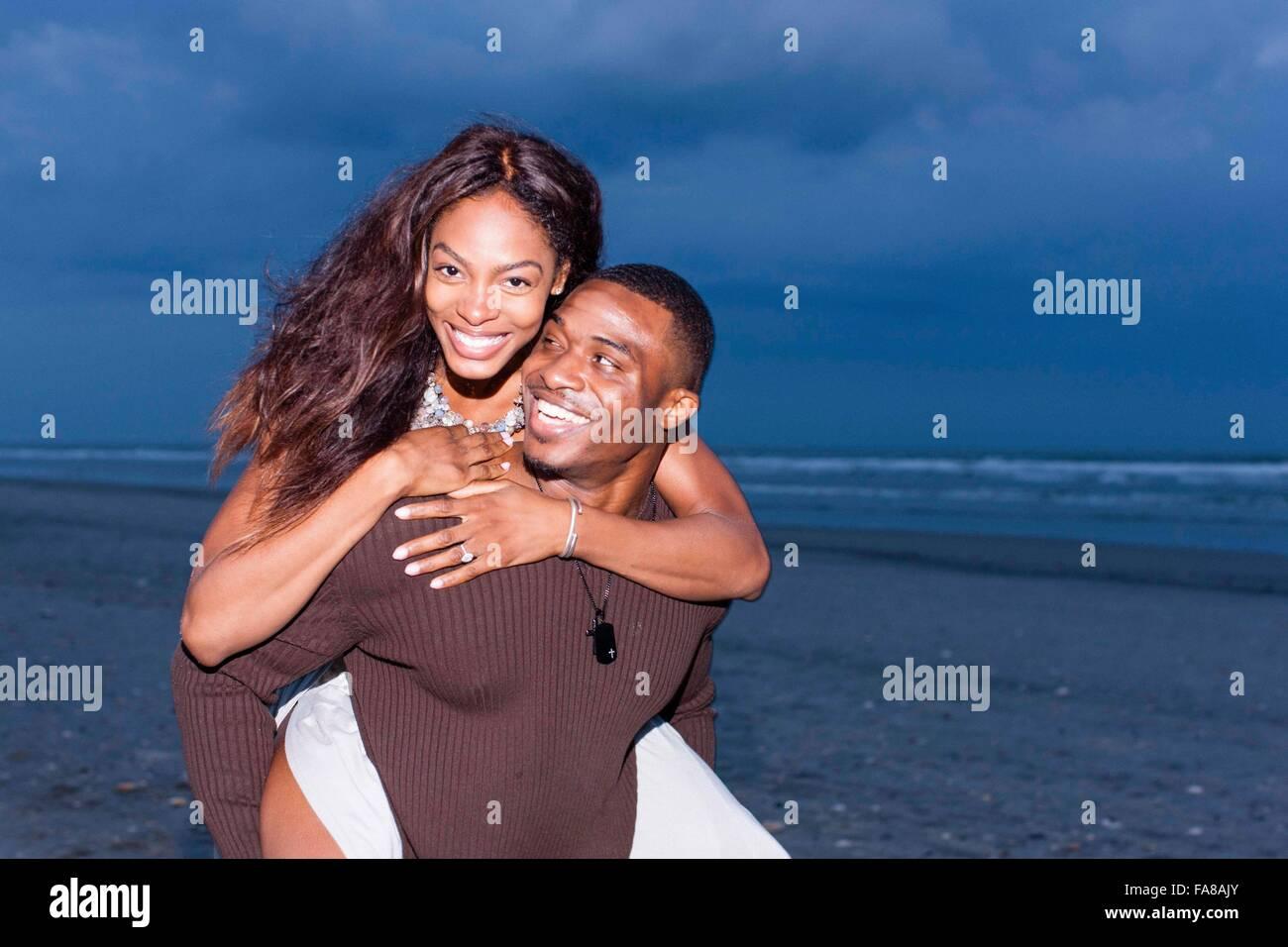 Par de playa, el hombre lleva una mujer en la espalda, sonriendo Foto de stock