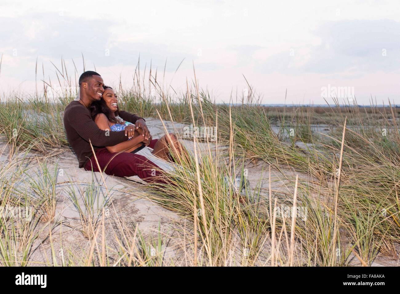 Par acostado en dunas de arena, un abrazo Foto de stock
