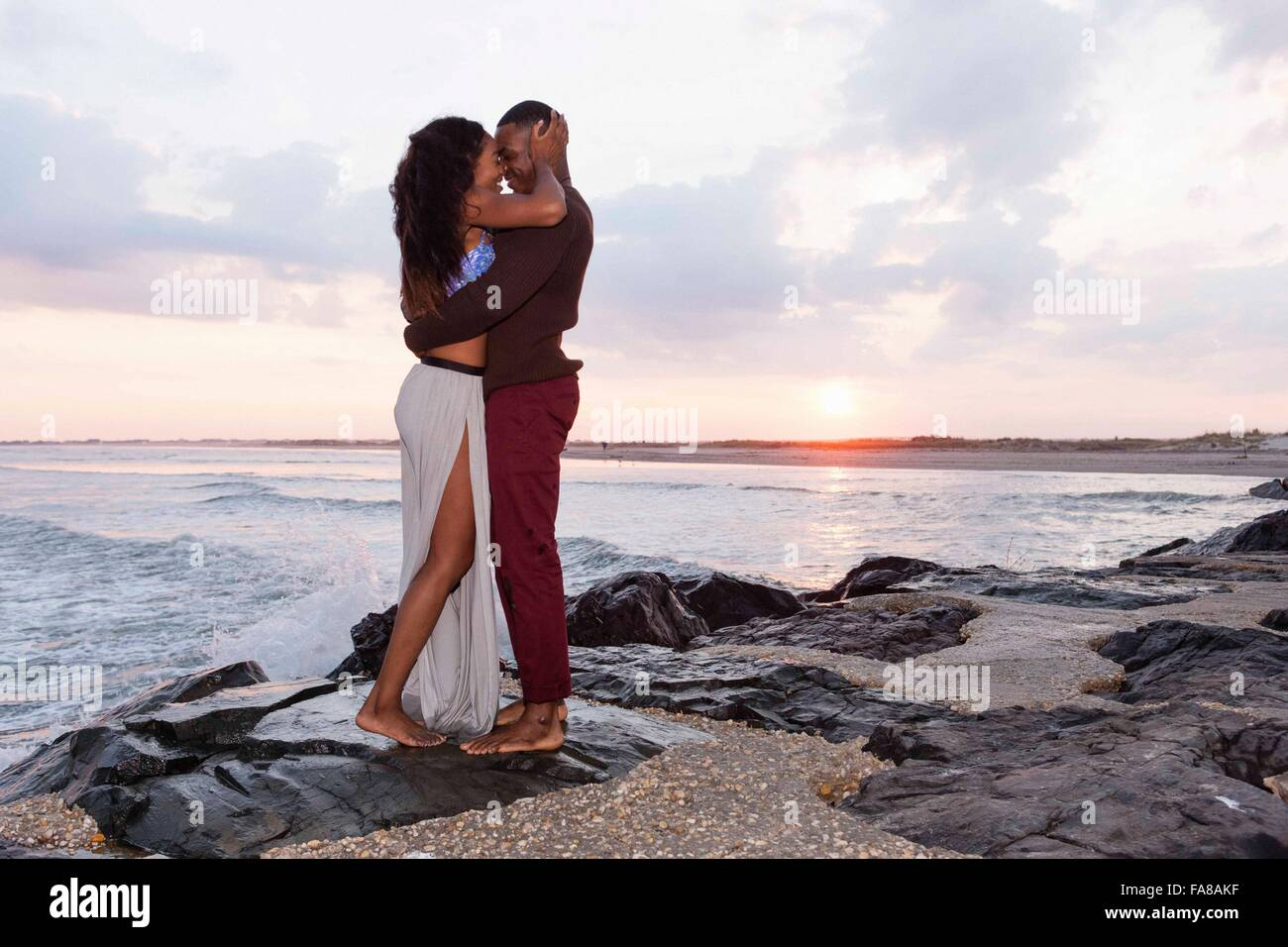 Par de pie en las rocas junto al mar, abrazarse, cara a cara. Foto de stock