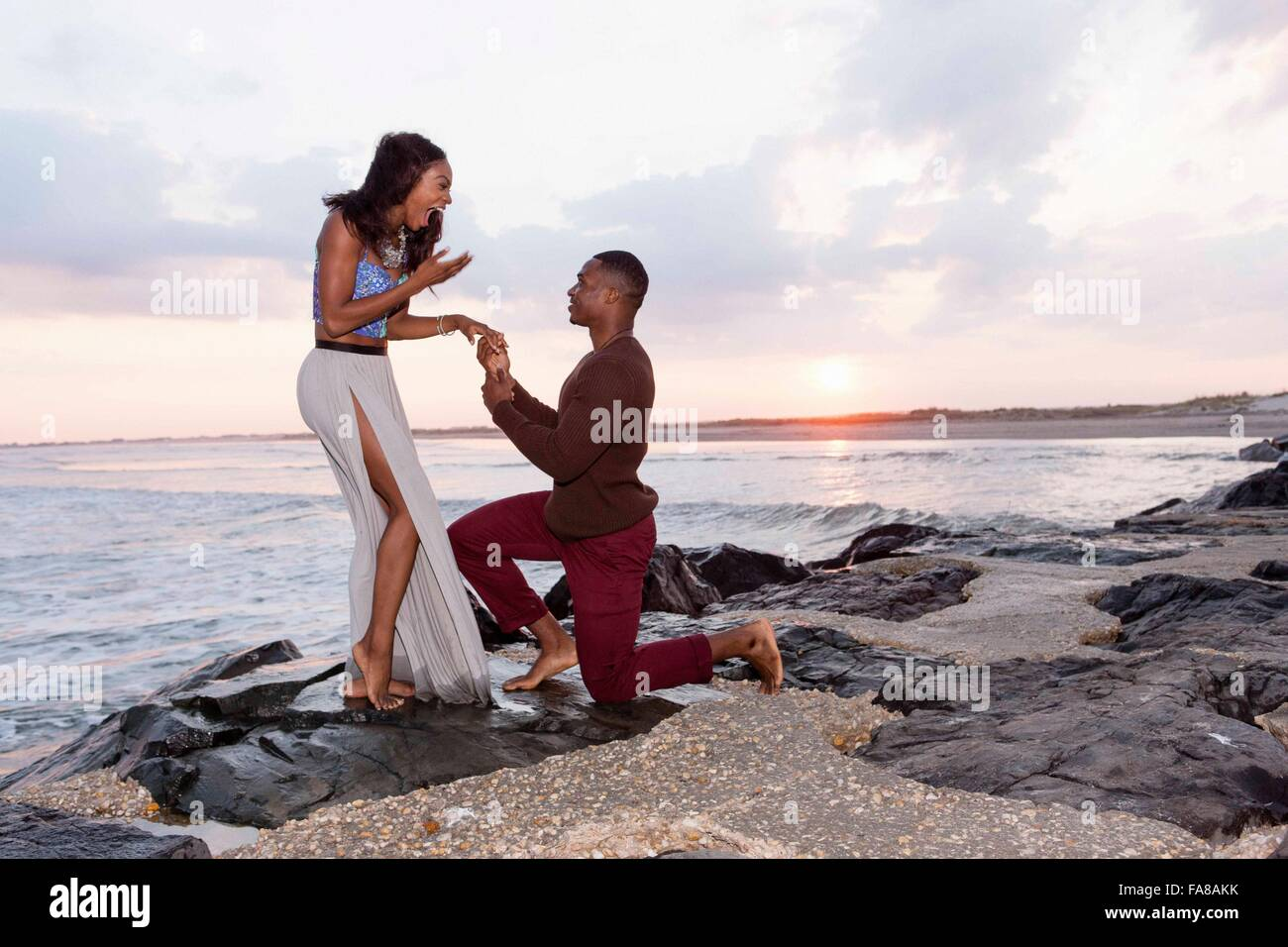 A mediados adulto hombre arrodillado en las rocas junto al mar, propone a la joven Foto de stock