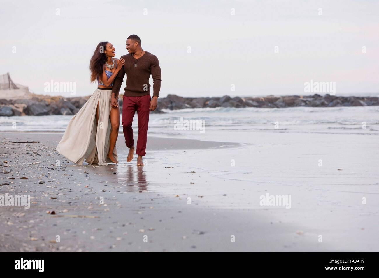 Pareja caminando por la playa, riendo Foto de stock