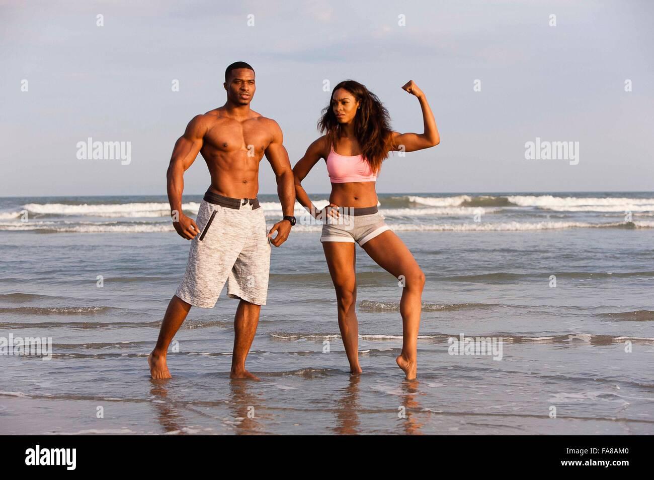 Pareja en la playa, estirando los músculos, posando Foto de stock