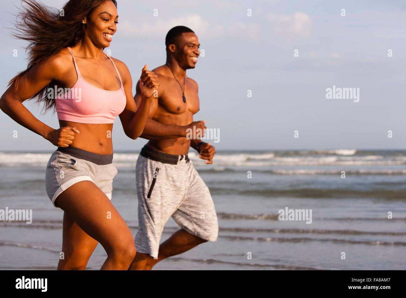 Par que corre a lo largo de la playa, sonriendo Foto de stock