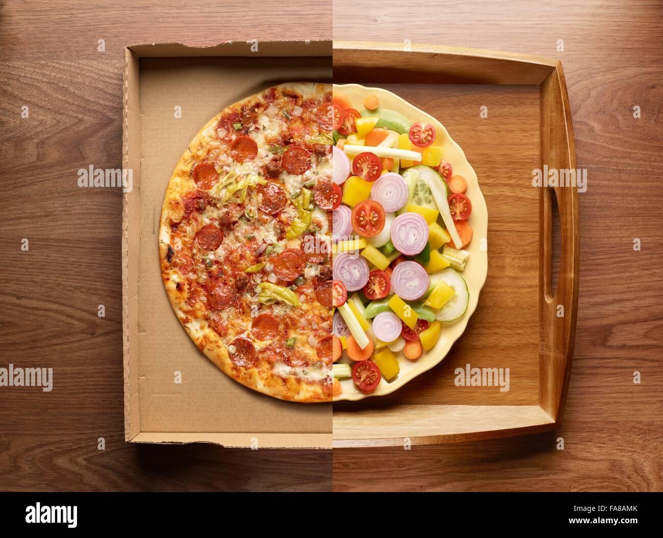 La mitad de la pizza, la mitad de las verduras en una placa, vista superior Foto de stock