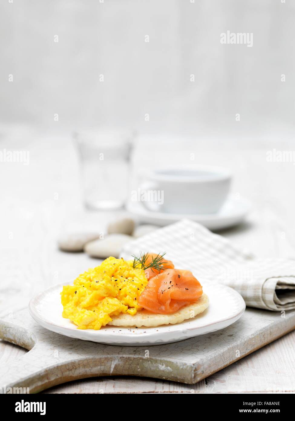 Salmón ahumado y huevos revueltos en blini aderezado con eneldo Foto de stock