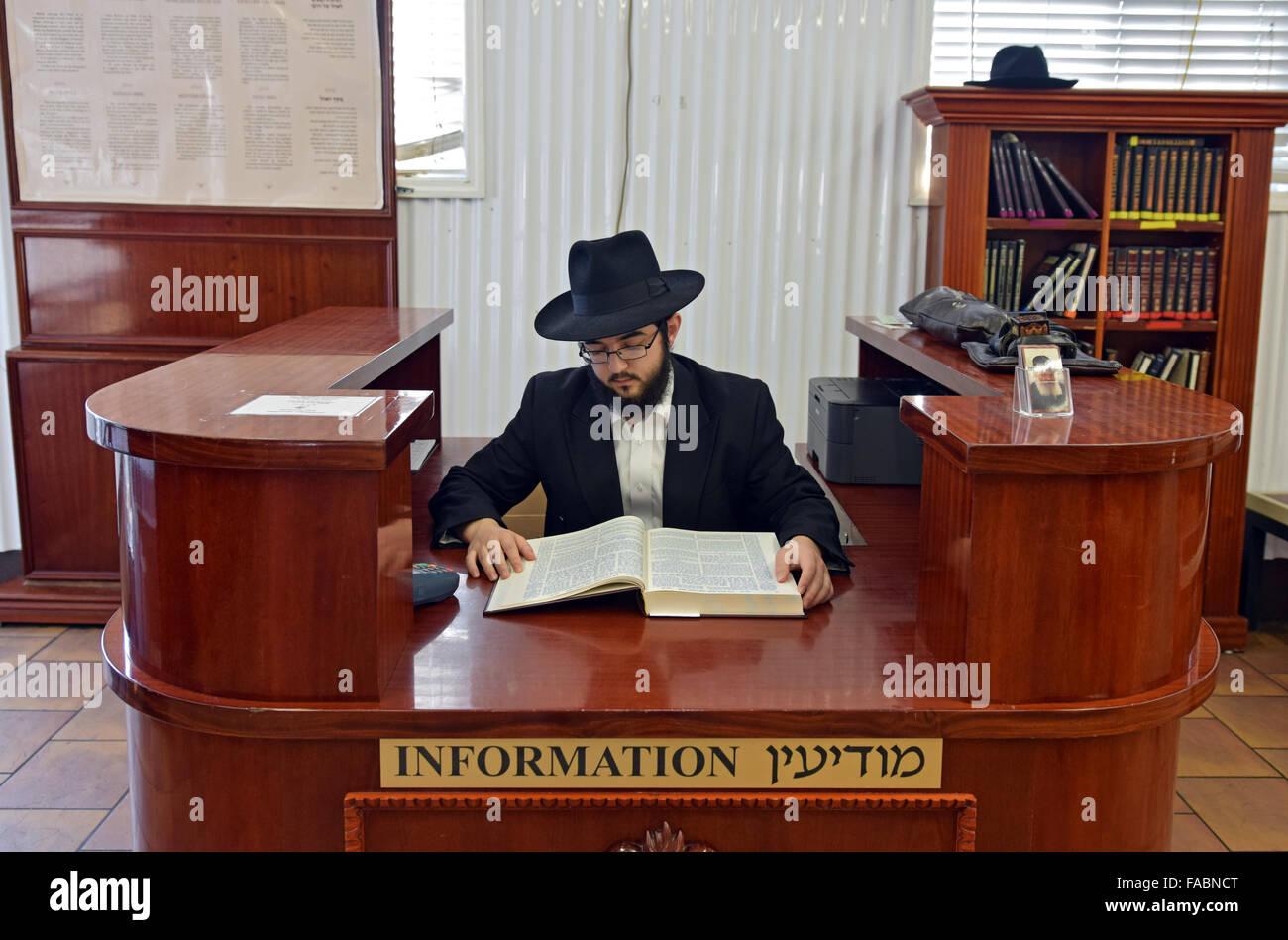 Un joven religioso judío estudiando Talmud como él está sentado en el mostrador de información Imagen De Stock