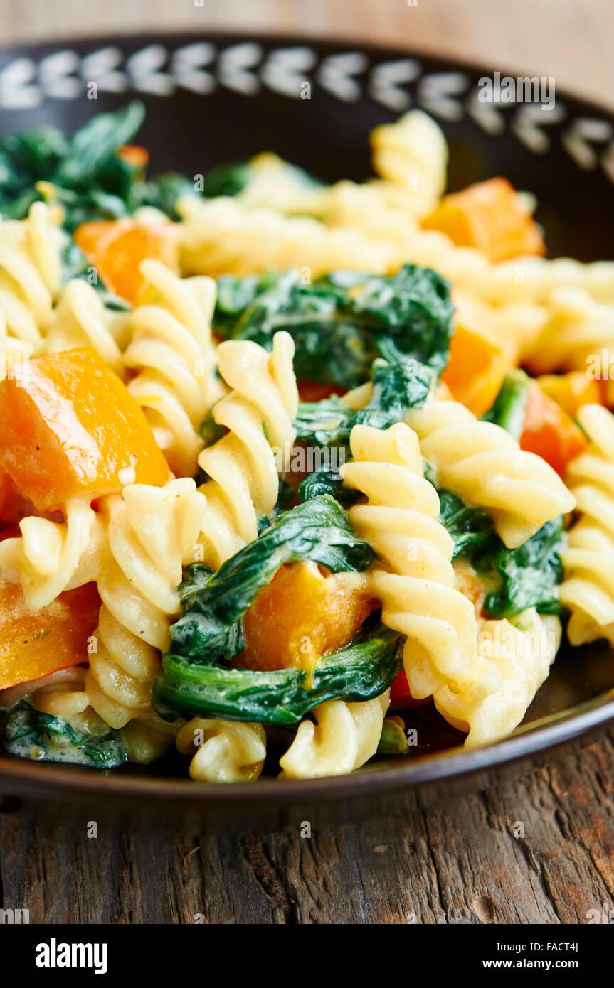 Plato de pasta con calabaza y espinacas. Imagen De Stock
