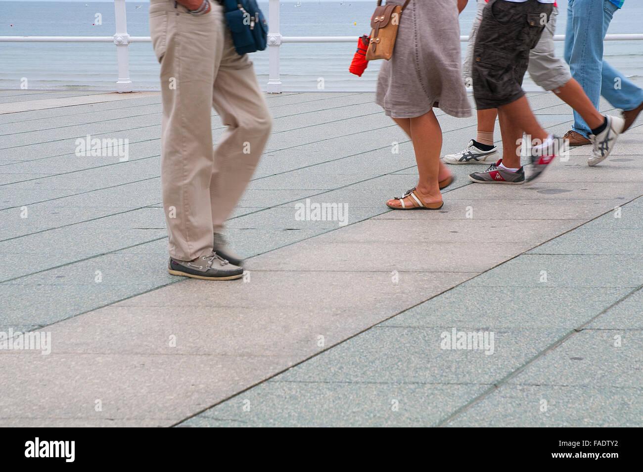 Las piernas de la gente caminando por el paseo marítimo. Gijon, Asturias, España. Imagen De Stock