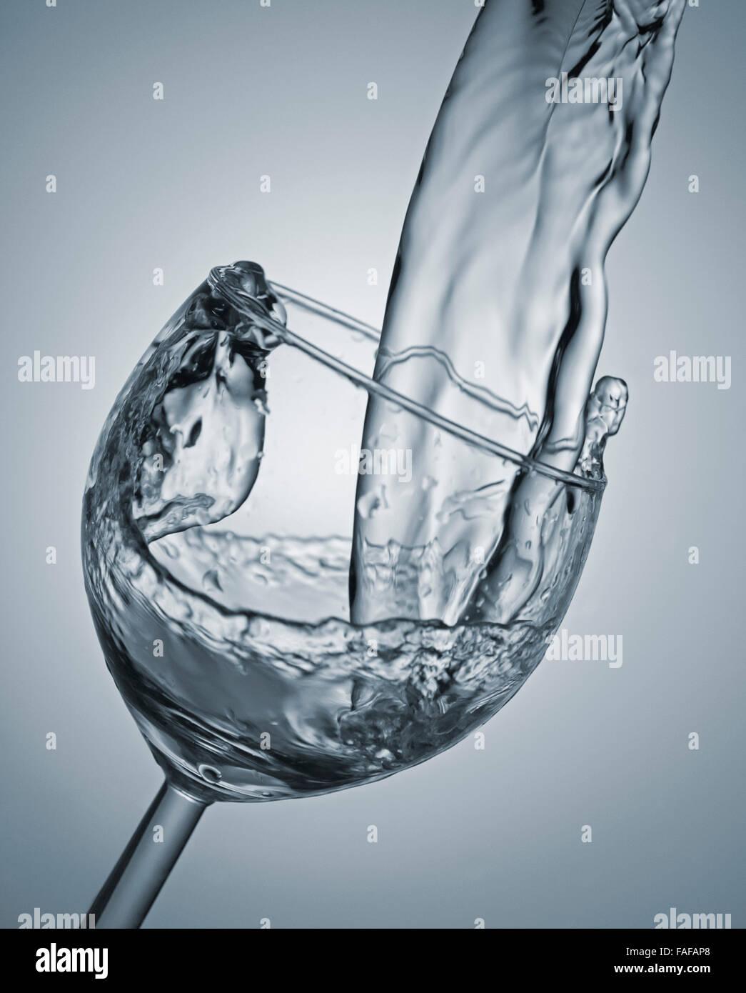 Un rush de verter agua en un vaso con faro y barcos dentro del caos Foto de stock