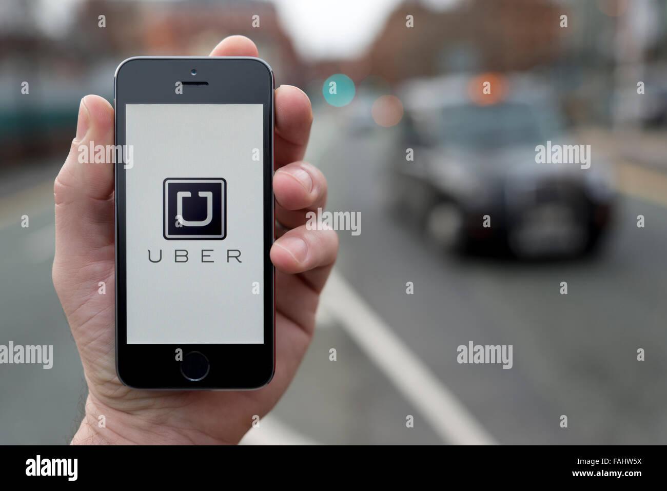 Un hombre usa el taxi Uber aplicación smartphone mientras estaba en una parada de taxis (uso Editorial solamente) Imagen De Stock