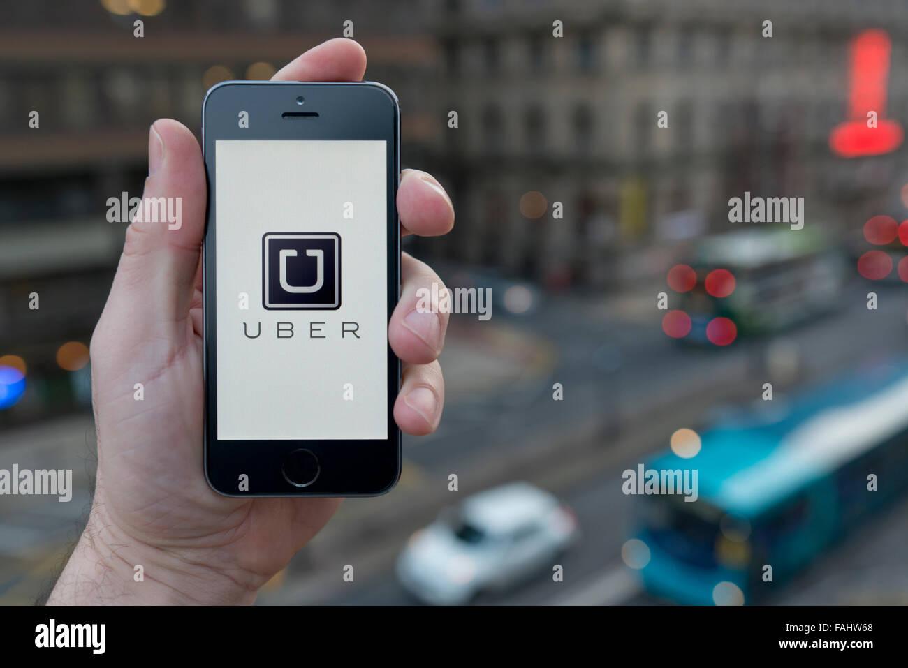 Un hombre usa el taxi Uber aplicación smartphone mientras estaba en un edificio alto con vistas a una concurrida Imagen De Stock