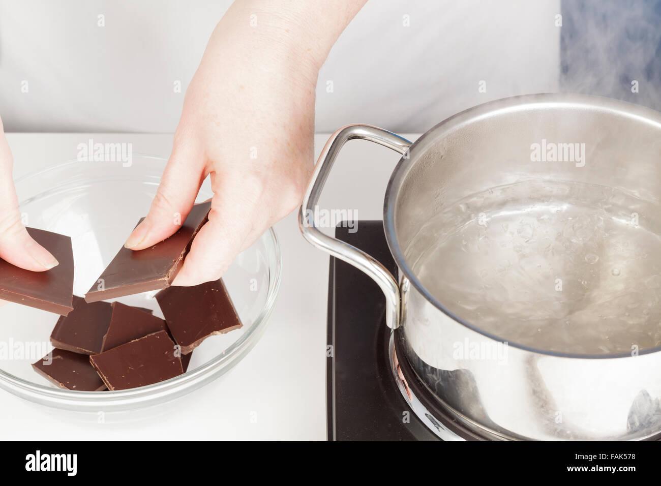 Romper el chocolate para derretir en baño maría Imagen De Stock