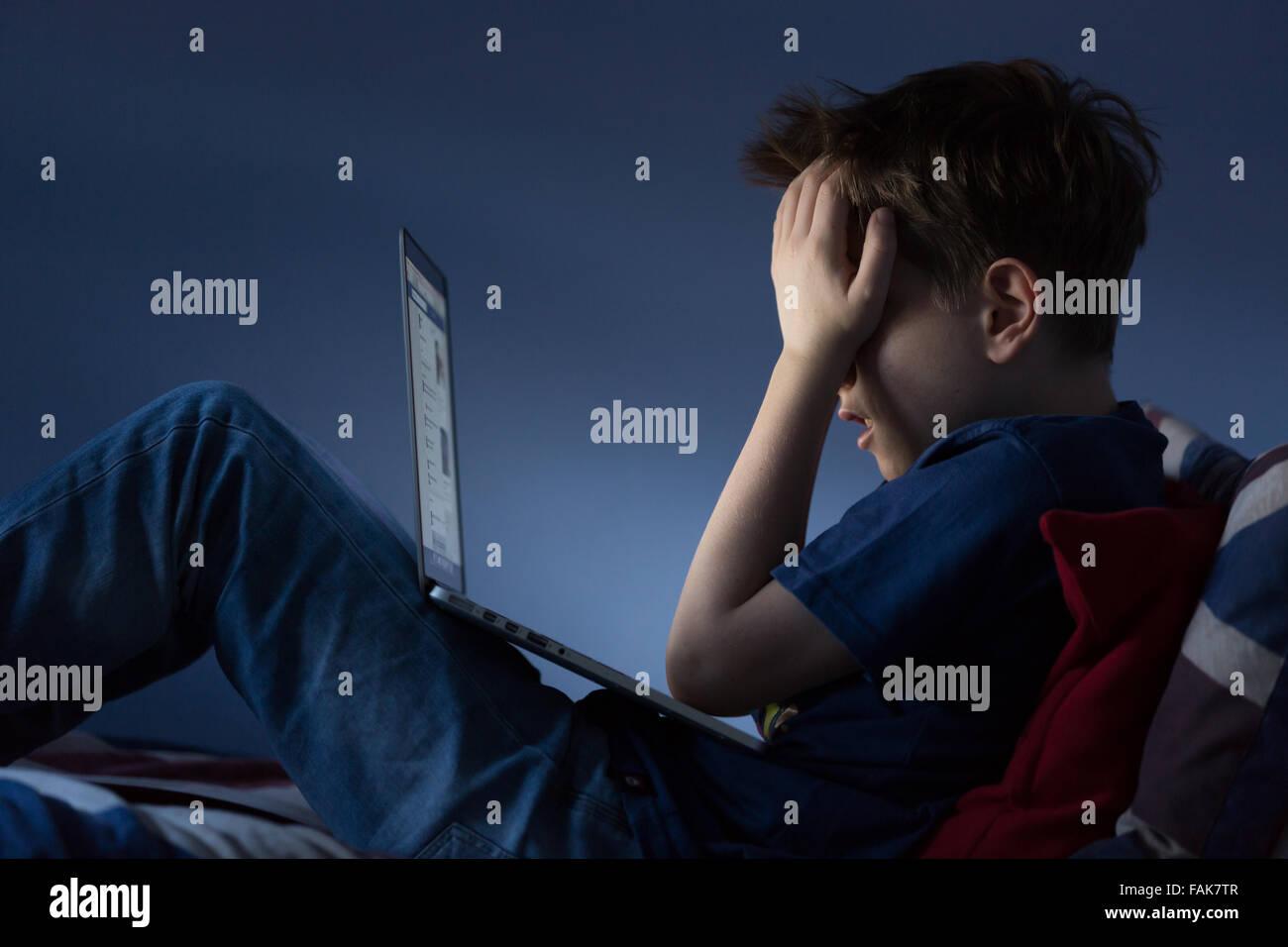 El acoso en línea Cyber Bullying foto de un malestar del muchacho en su habitación mirando mensajes hirientes Imagen De Stock