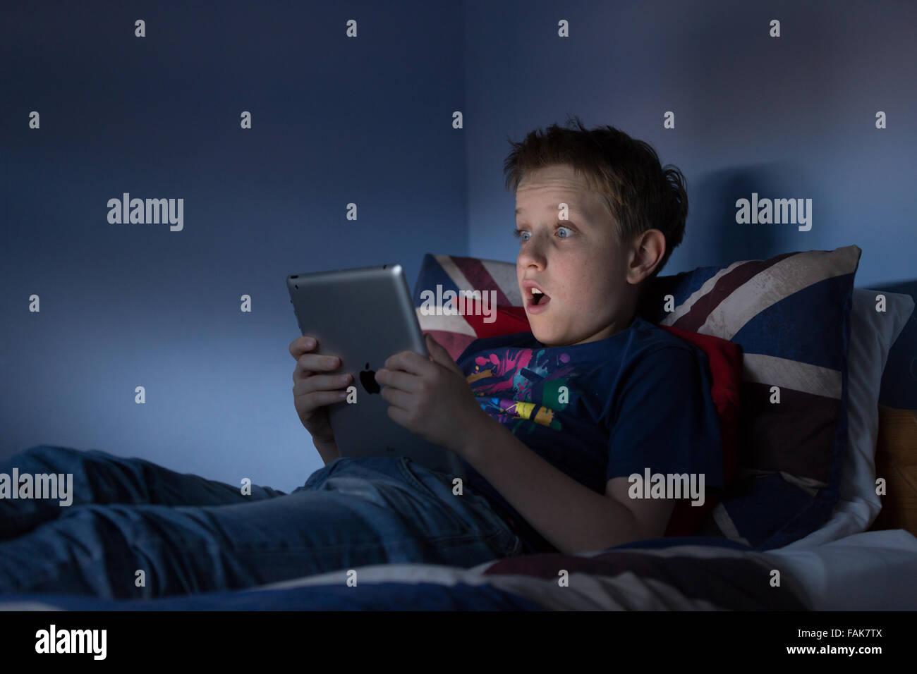 Un muchacho sentado hasta tarde en su dormitorio, buscando en internet, consternado por lo que él está Imagen De Stock