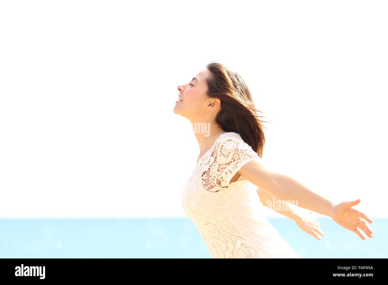 Mujer alegre y disfrutando del viento y respirar aire fresco en la playa en un día soleado y ventoso Foto de stock