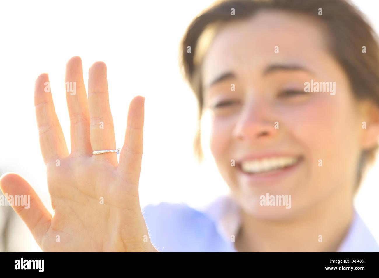 Feliz mujer mirando una anillo de compromiso después de la propuesta en un día soleado Imagen De Stock
