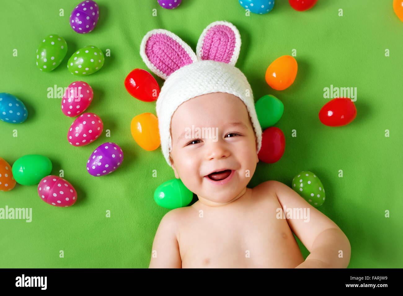 Baby Boy en bunny hat acostado sobre una manta verde con huevos de Pascua Imagen De Stock