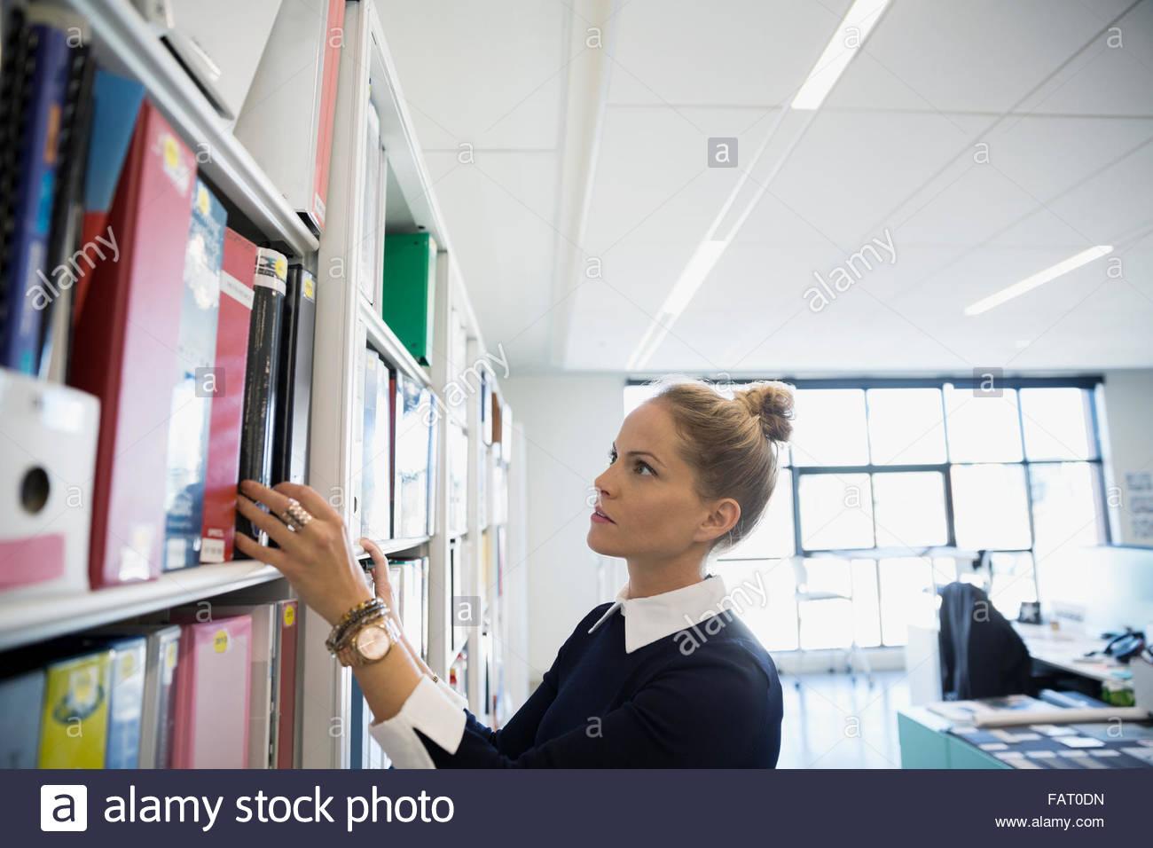 Arquitecto buscando libro en biblioteca de Office Imagen De Stock