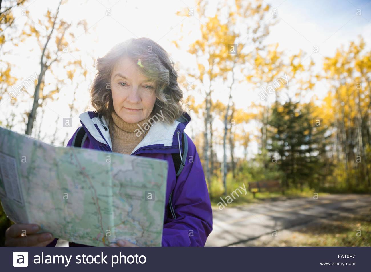 Mujer senderismo control de mapa en otoño woods Imagen De Stock