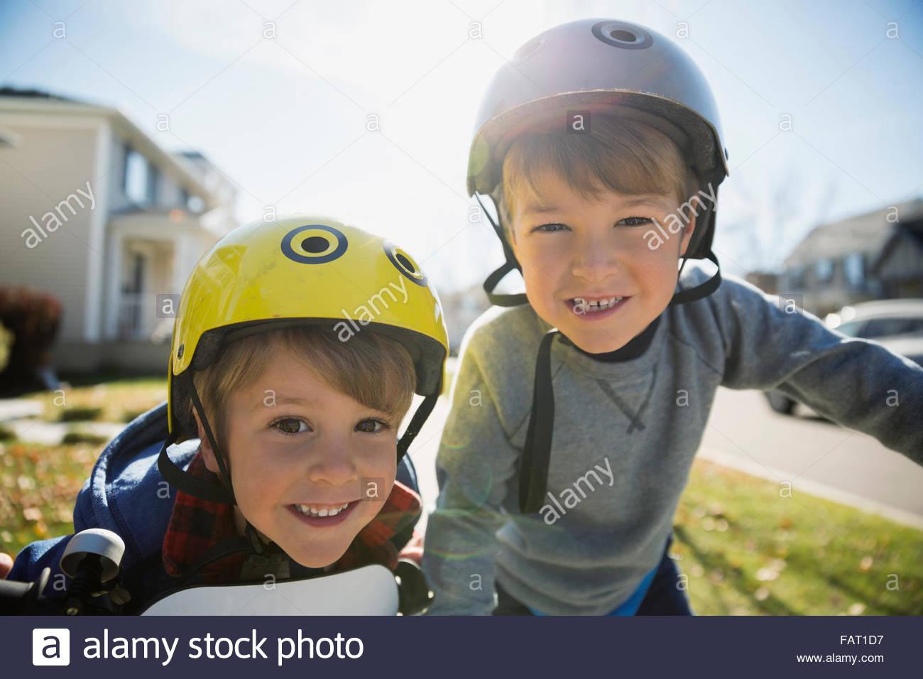 Retrato sonriente hermanos con cascos Imagen De Stock