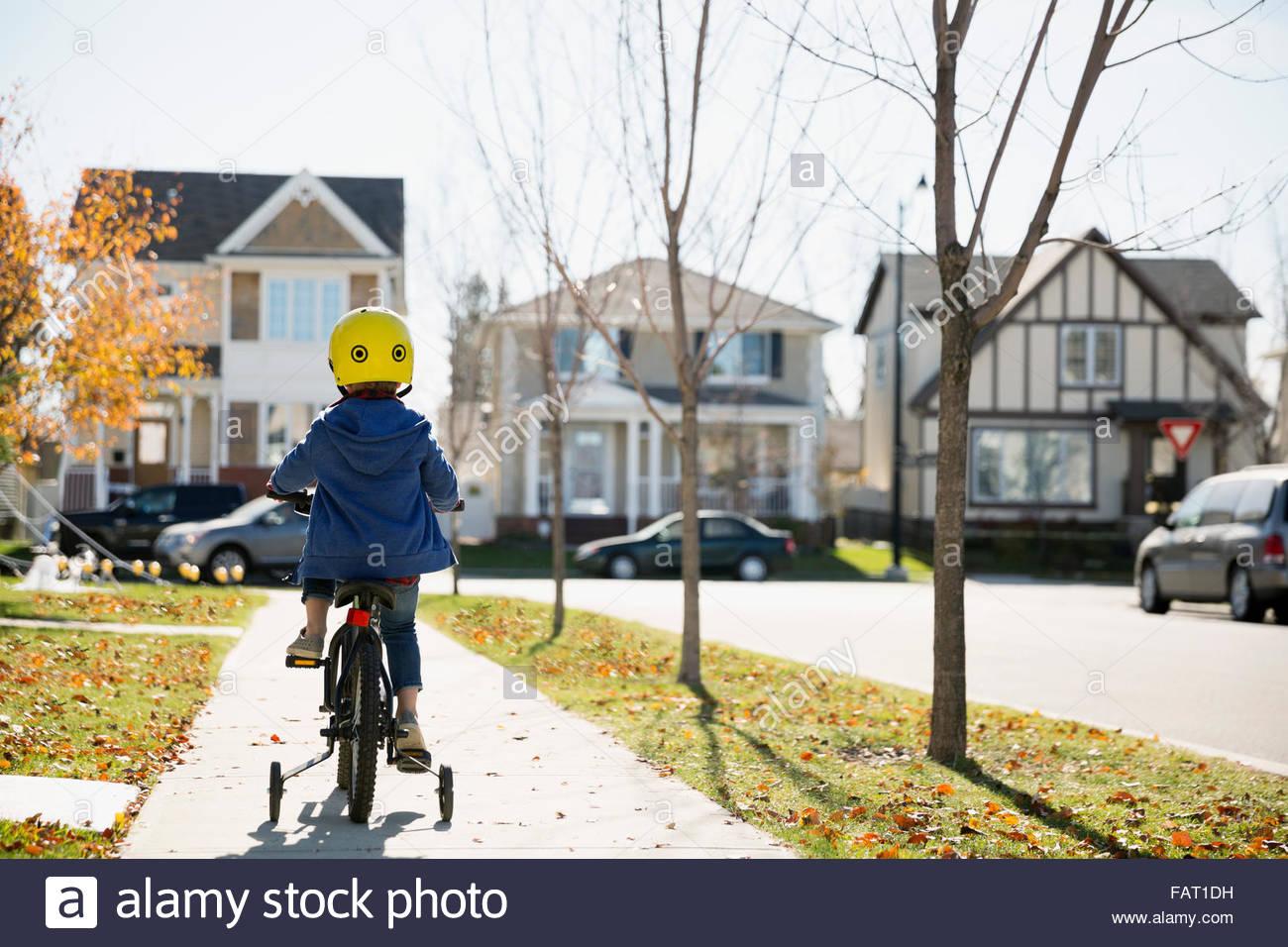 Vista trasera boy montando bicicleta otoño barrio acera Imagen De Stock