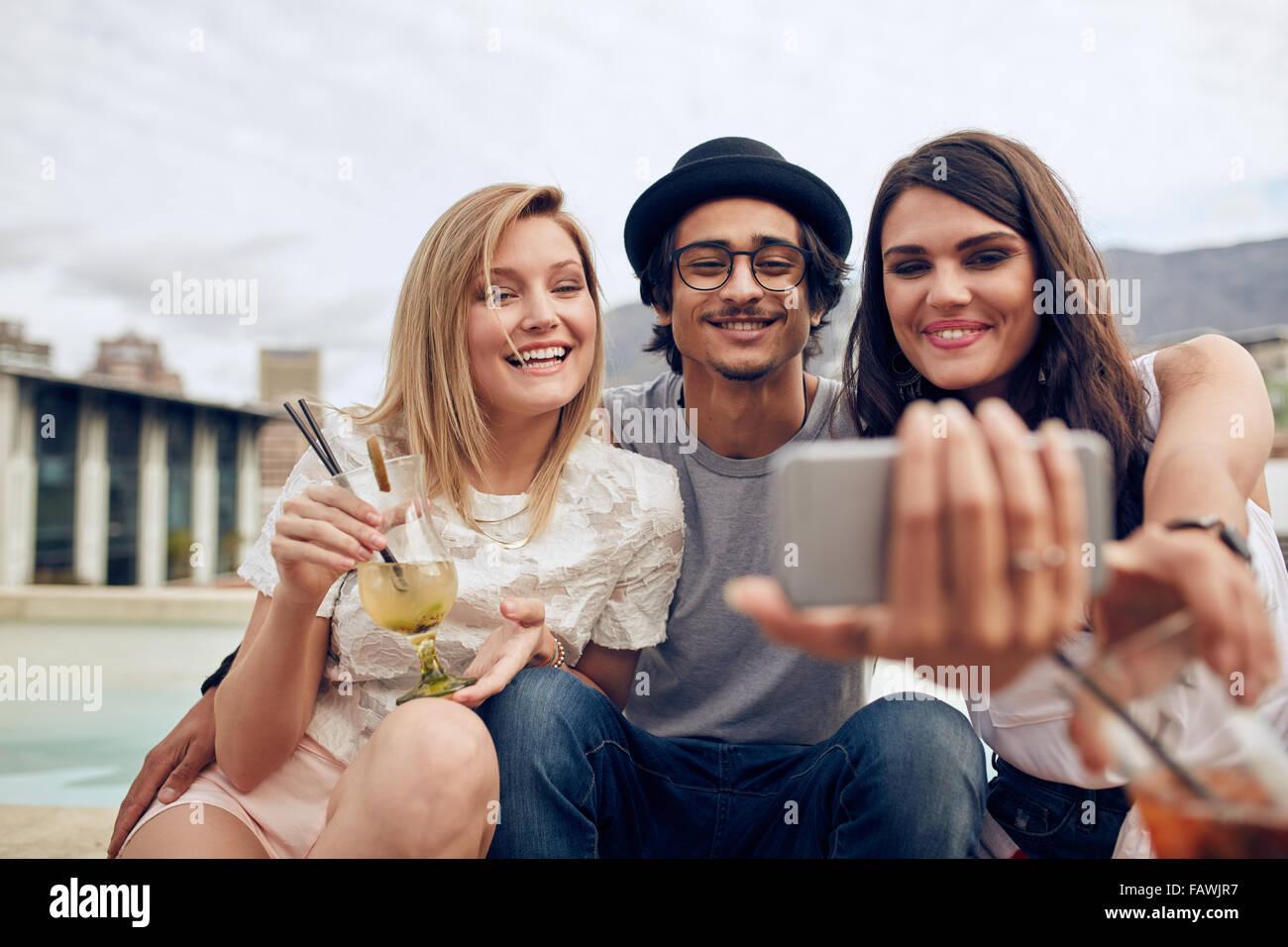 Jóvenes tomando autorretrato con teléfono inteligente durante una fiesta. Los jóvenes hombres y mujeres teniendo selfie en parte en la azotea. O colgantes Foto de stock