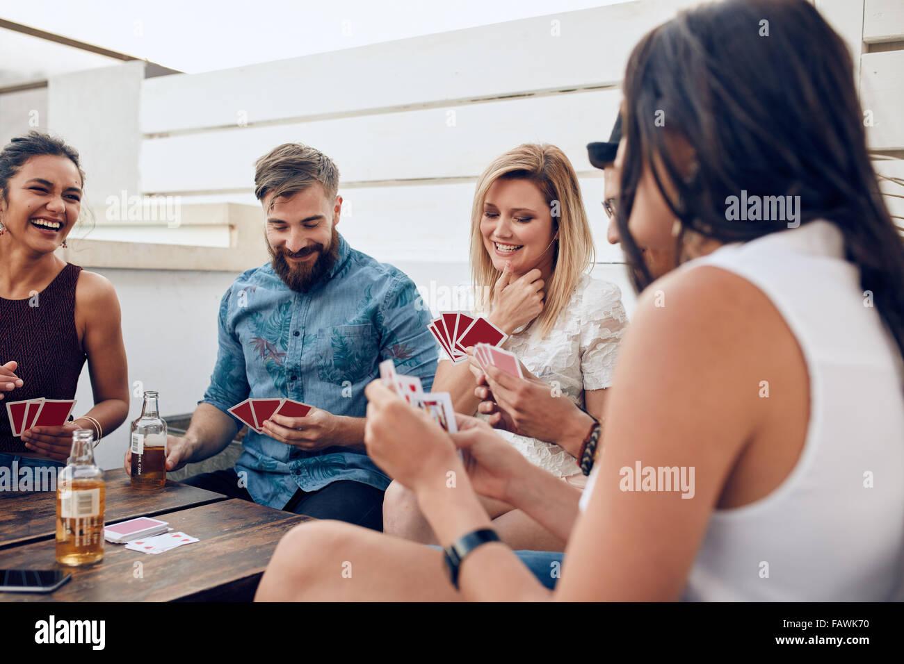 Grupo de Amigos sentados en una mesa de madera y jugando a las cartas. Los jóvenes jugando un juego de cartas Imagen De Stock