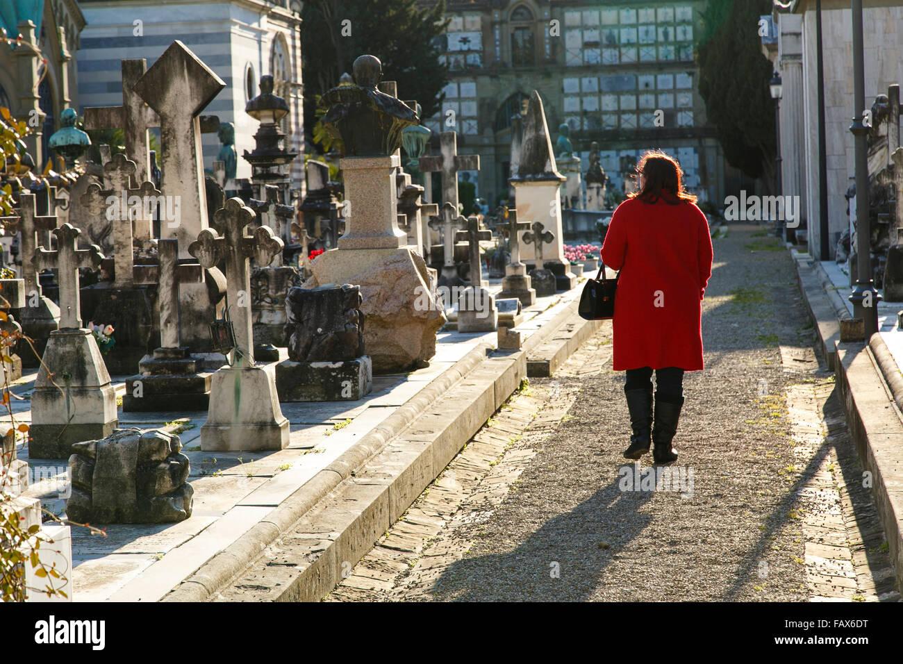 Mujer con abrigo rojo sobriamente caminando por el cementerio de Florencia, Italia. Foto de stock