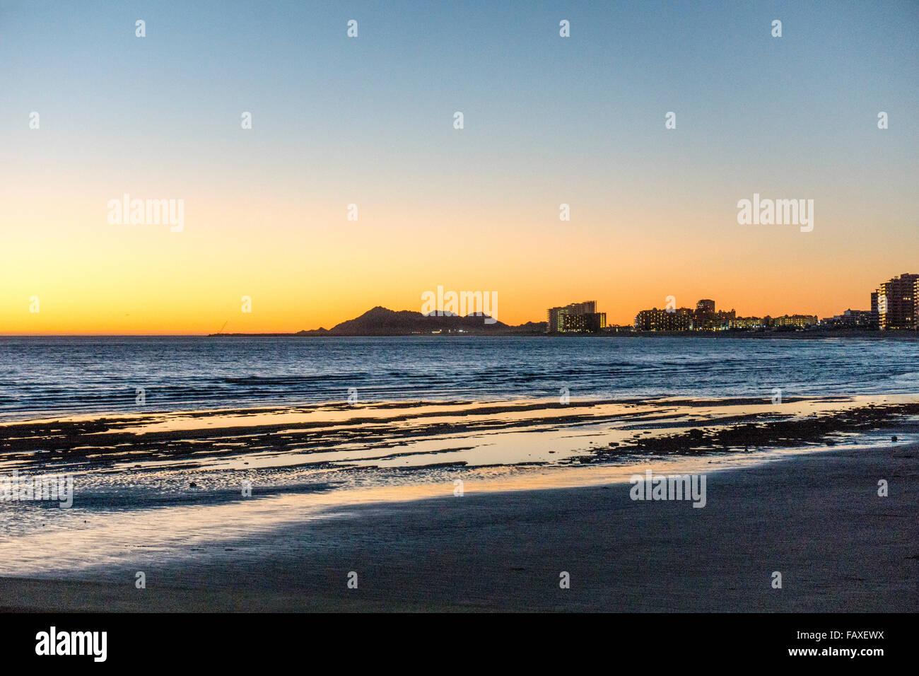 Puesta de sol sobre el mar de Cortez, visto desde Playa Bonita como retrocediendo marea revela su fondo pedregoso Imagen De Stock