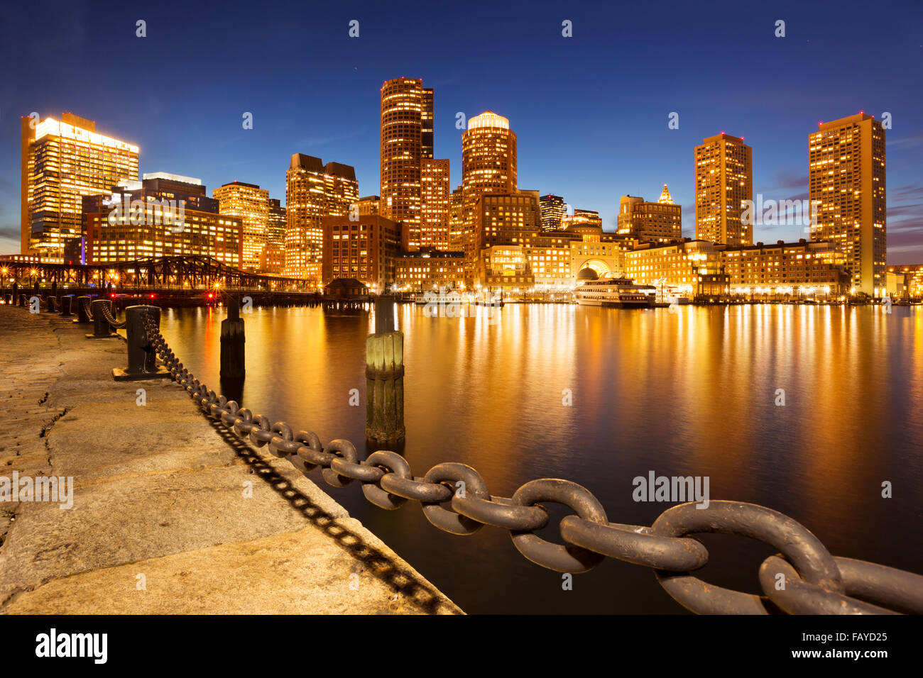 El horizonte del centro de Boston, Massachusetts a través del agua al atardecer. Imagen De Stock