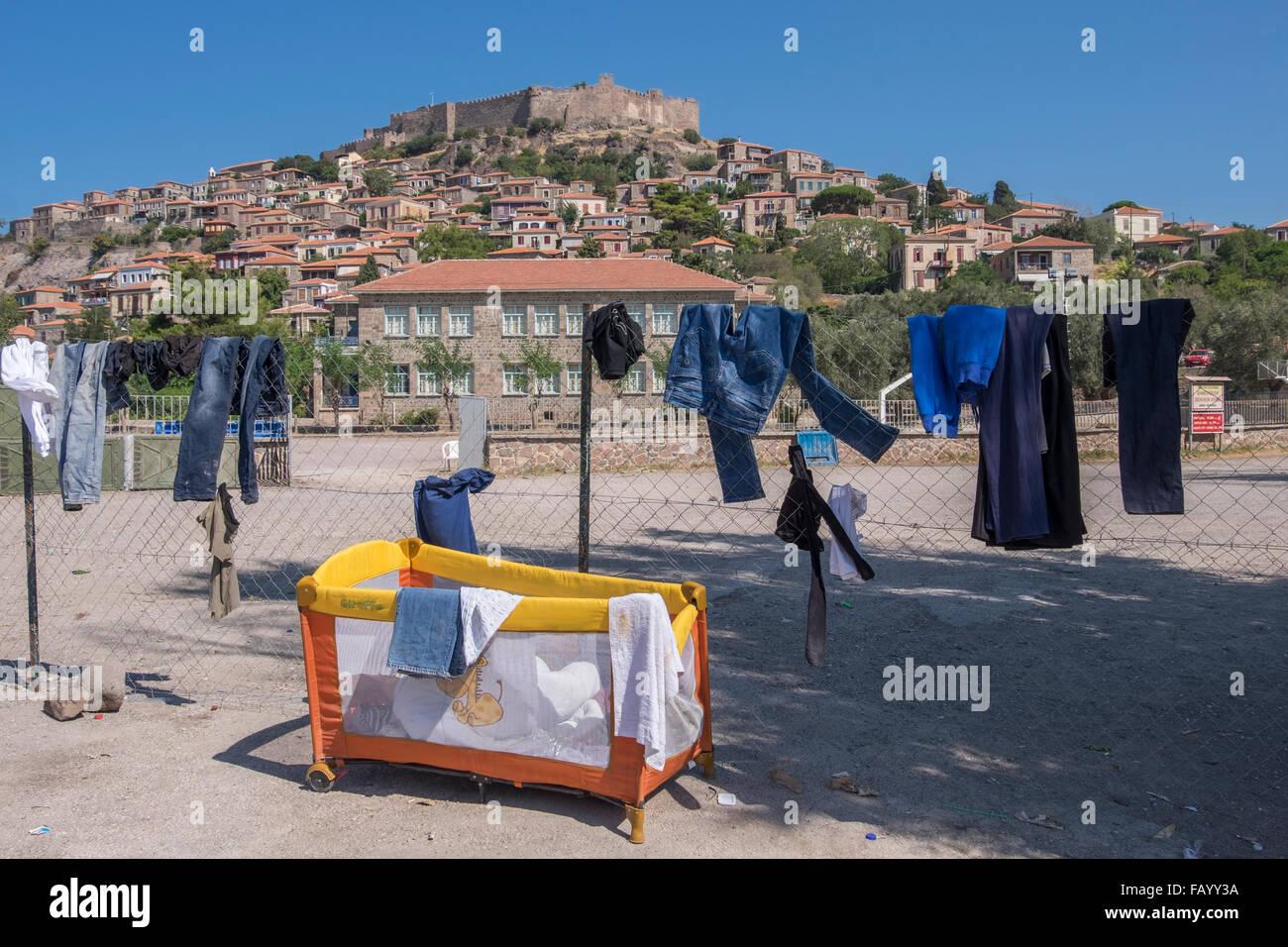 Las ropas de los refugiados recientemente llegados de secado en una valla y una cuna del bebé en el borde de la Foto de stock