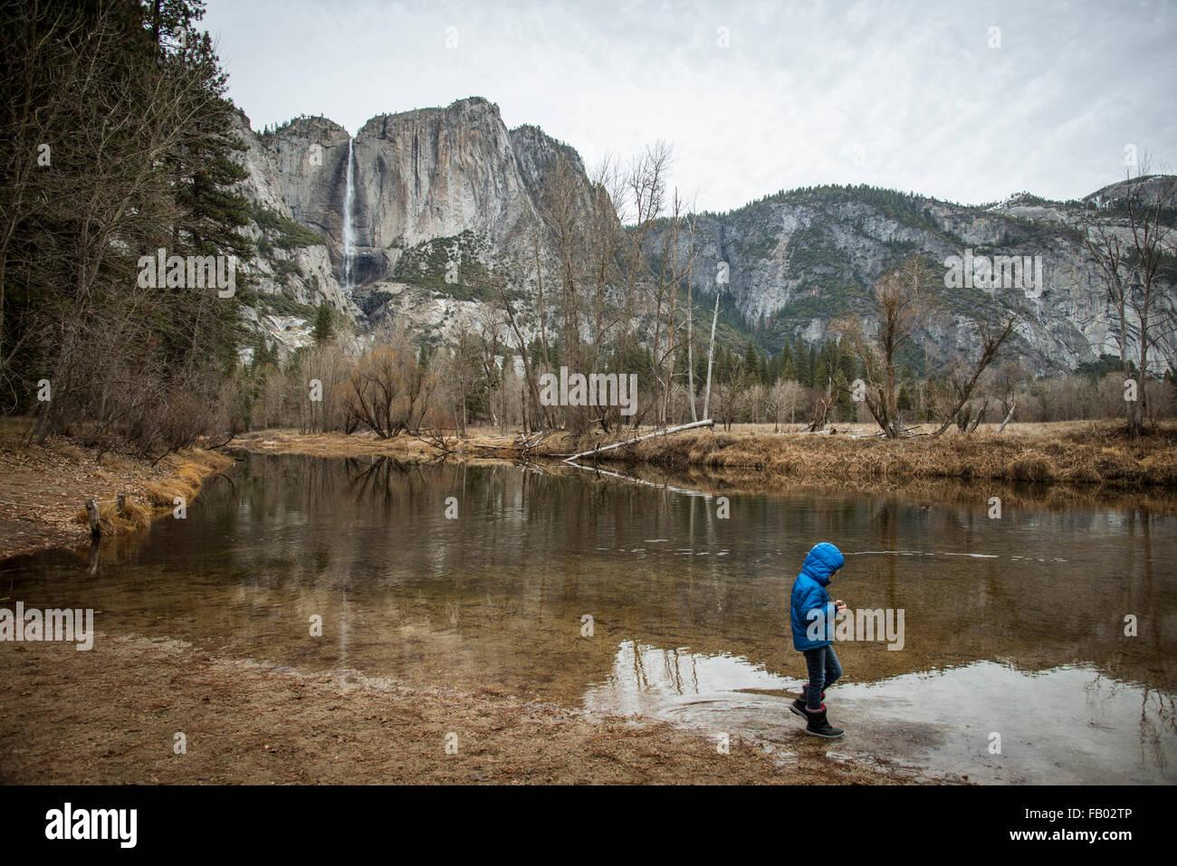 Niño caminando por el borde del río en el valle de Yosemite en otoño.Vistiendo un abrigo azul con capucha, cerca Foto de stock