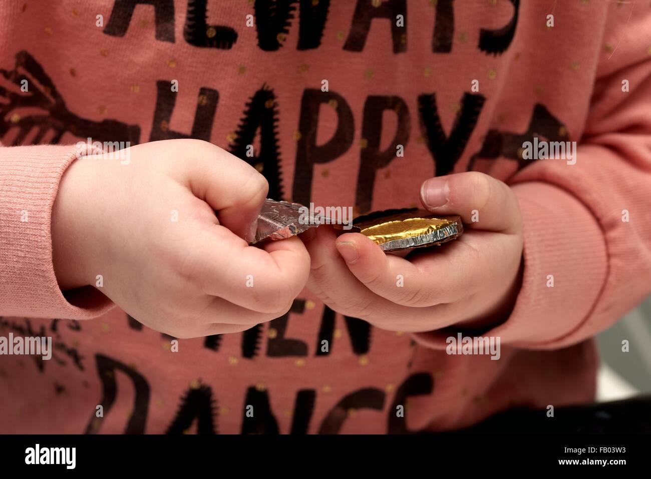 Una niña de tres años desenvolver una moneda de chocolate Imagen De Stock