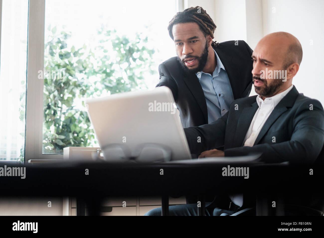 Dos hombres de negocios que trabajan con ordenador portátil mediante la recepción en la oficina Foto de stock