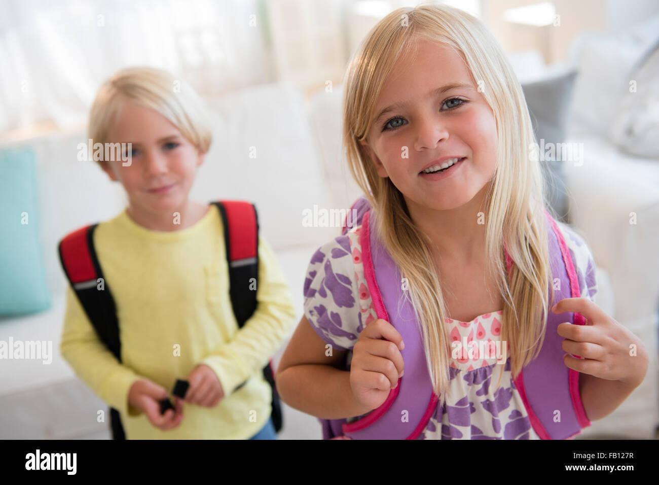 Chico y chica (4-5) (6-7) con mochilas, mirando a la cámara Imagen De Stock