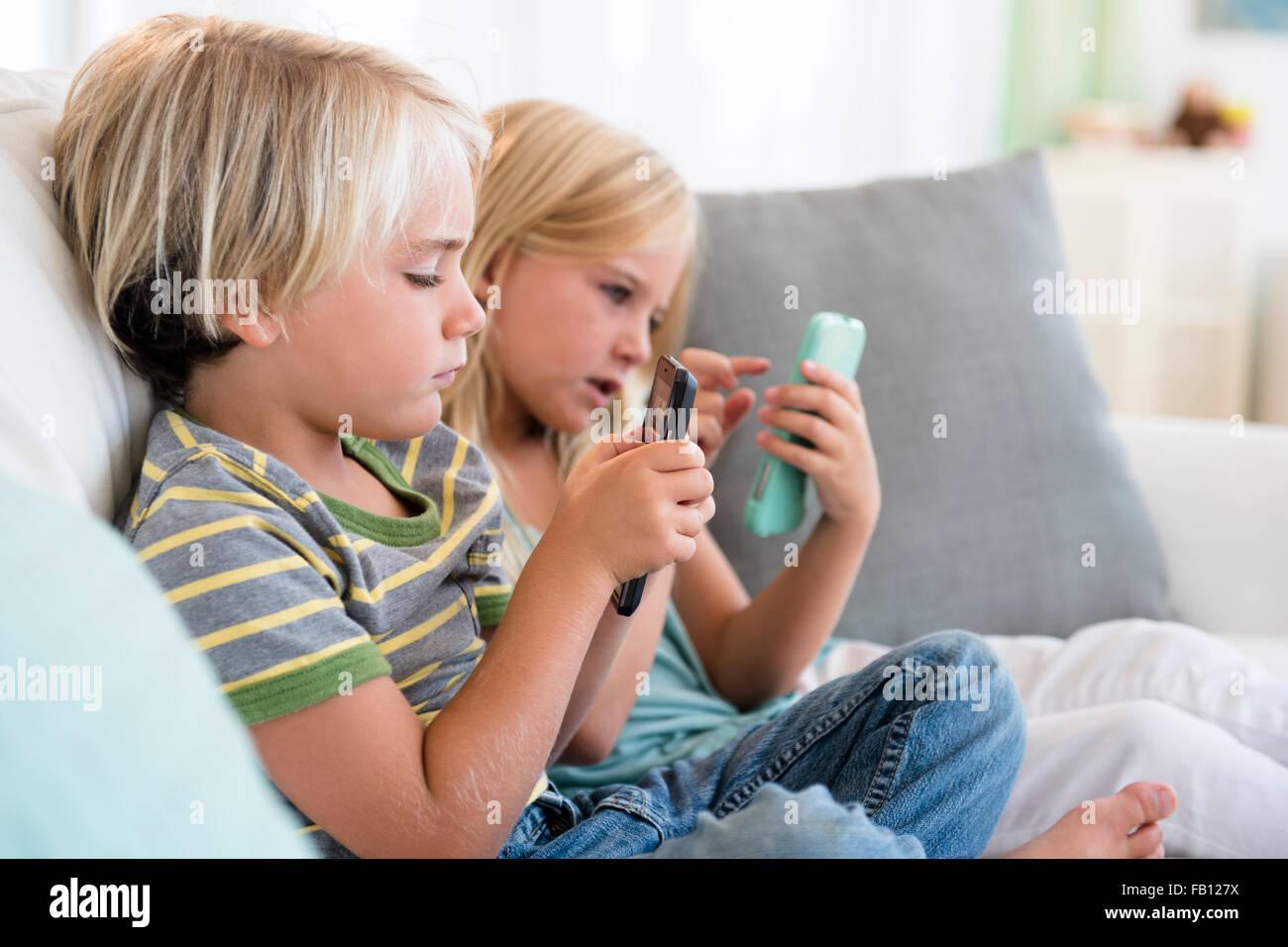 Chico y chica (4-5) (6-7) jugando juegos en teléfonos inteligentes. Imagen De Stock