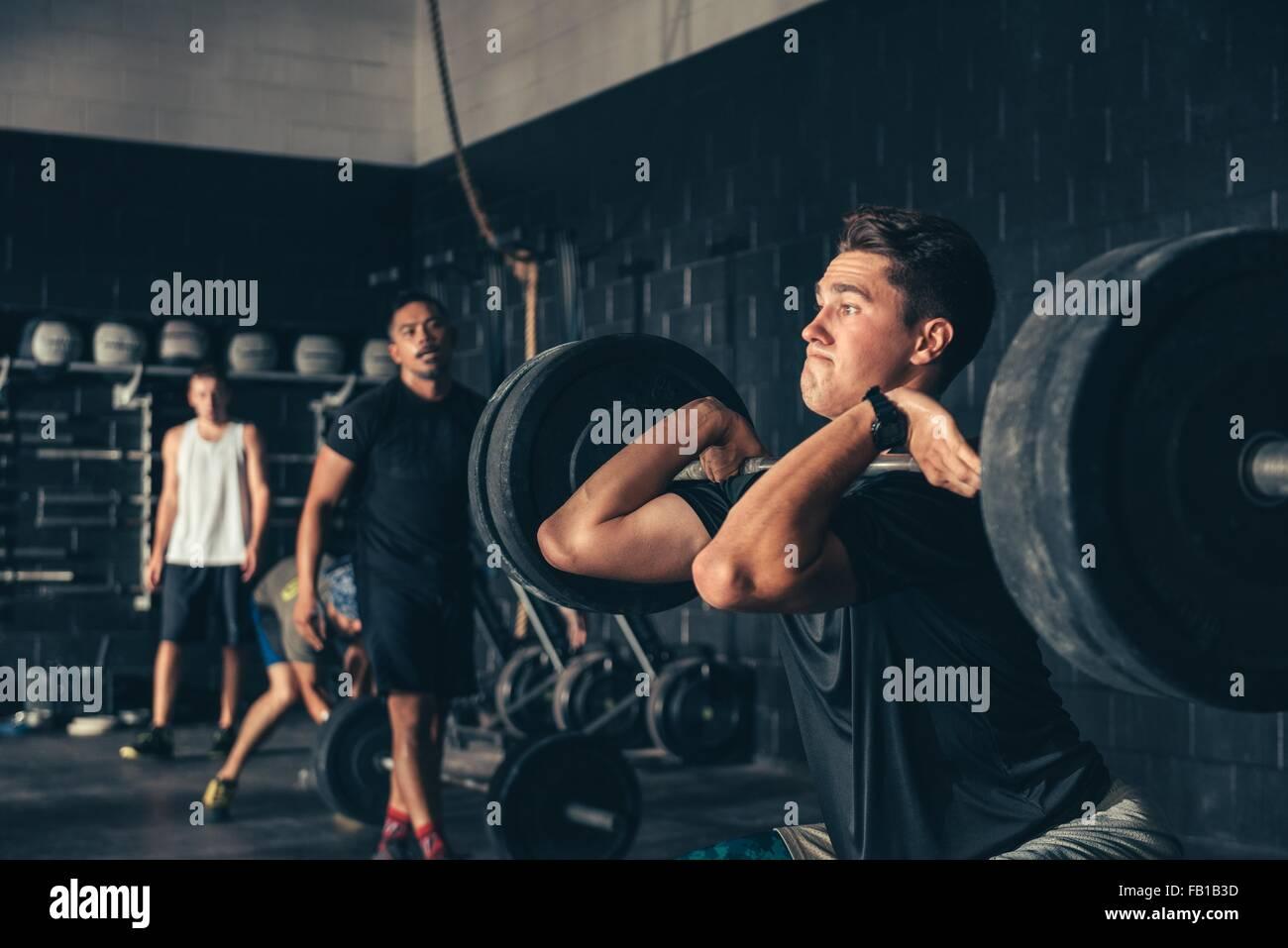 Hombre y entrenamiento con barbell en gimnasio Foto de stock