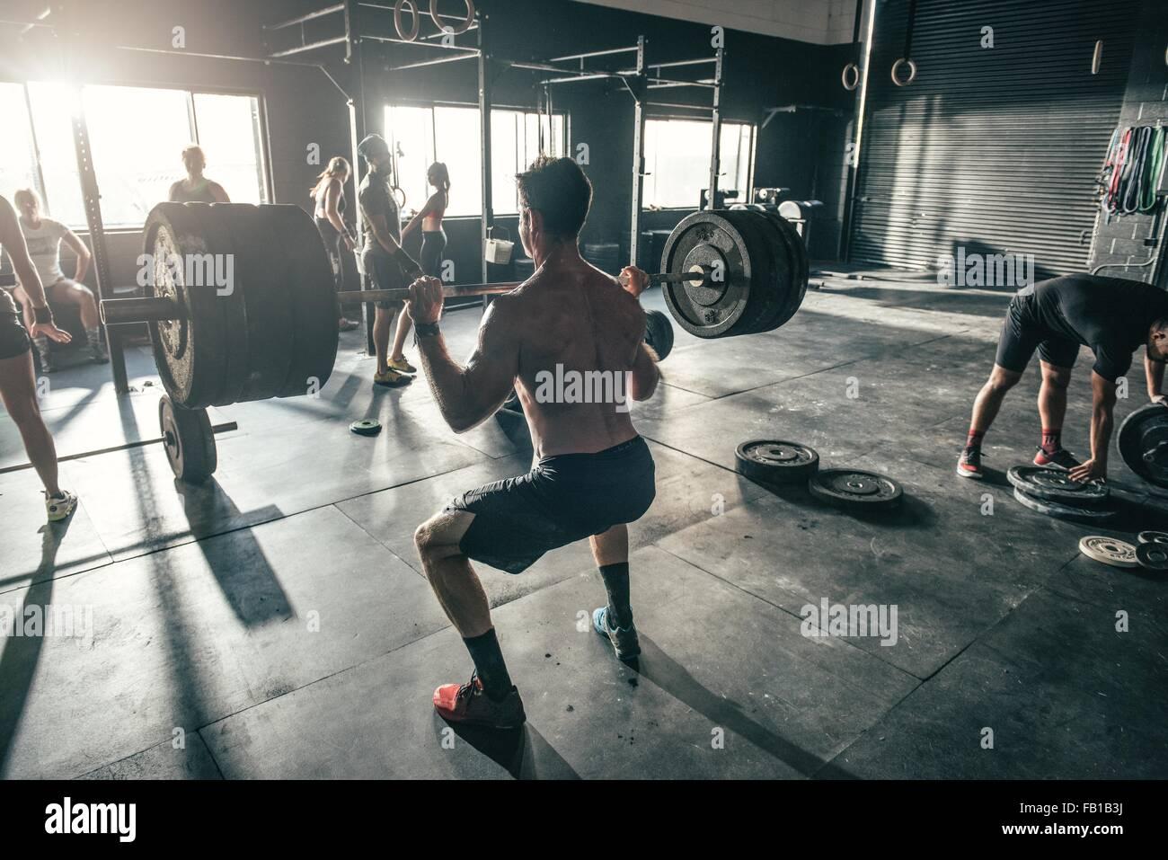 Hombre con formación barbell en gimnasio Imagen De Stock