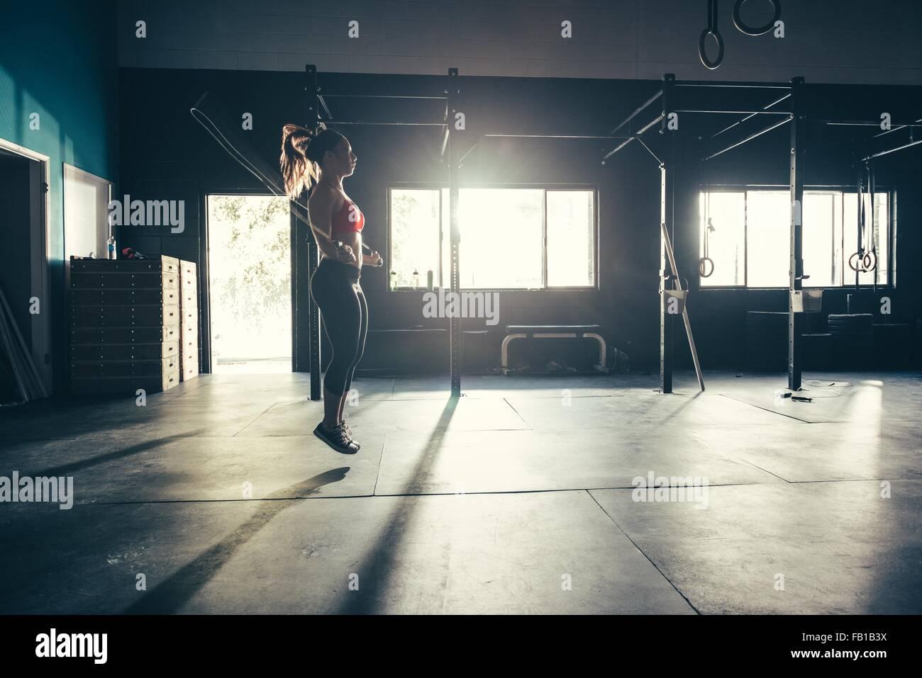 Mujer saltando con cuerdas de saltar en el gimnasio Imagen De Stock