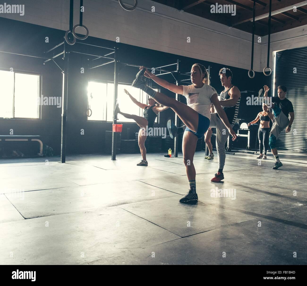 Los hombres y mujeres ejerzan juntos en el gimnasio Imagen De Stock