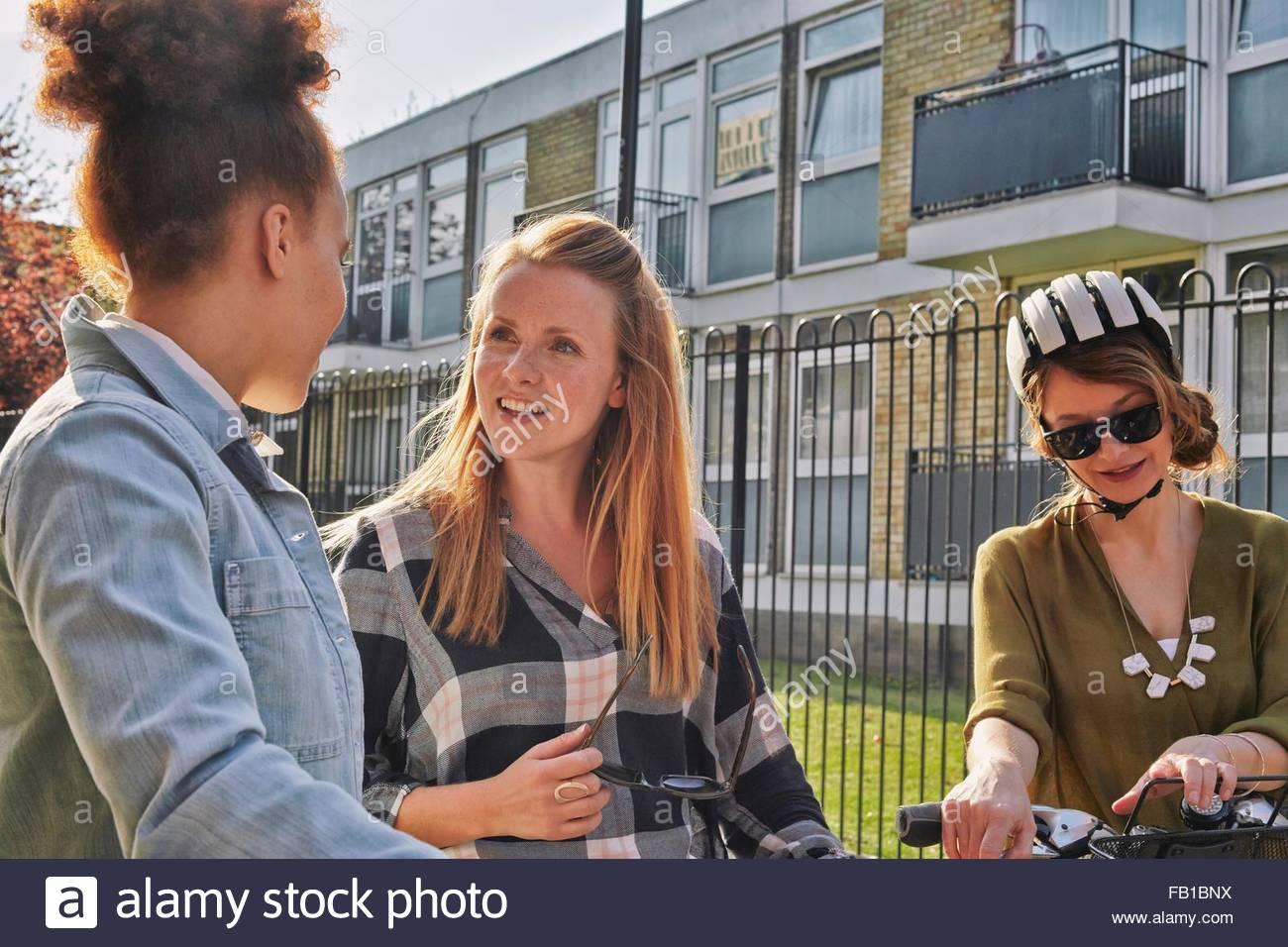 Las mujeres en el área urbana, de cintura para arriba, de pie charlando Imagen De Stock
