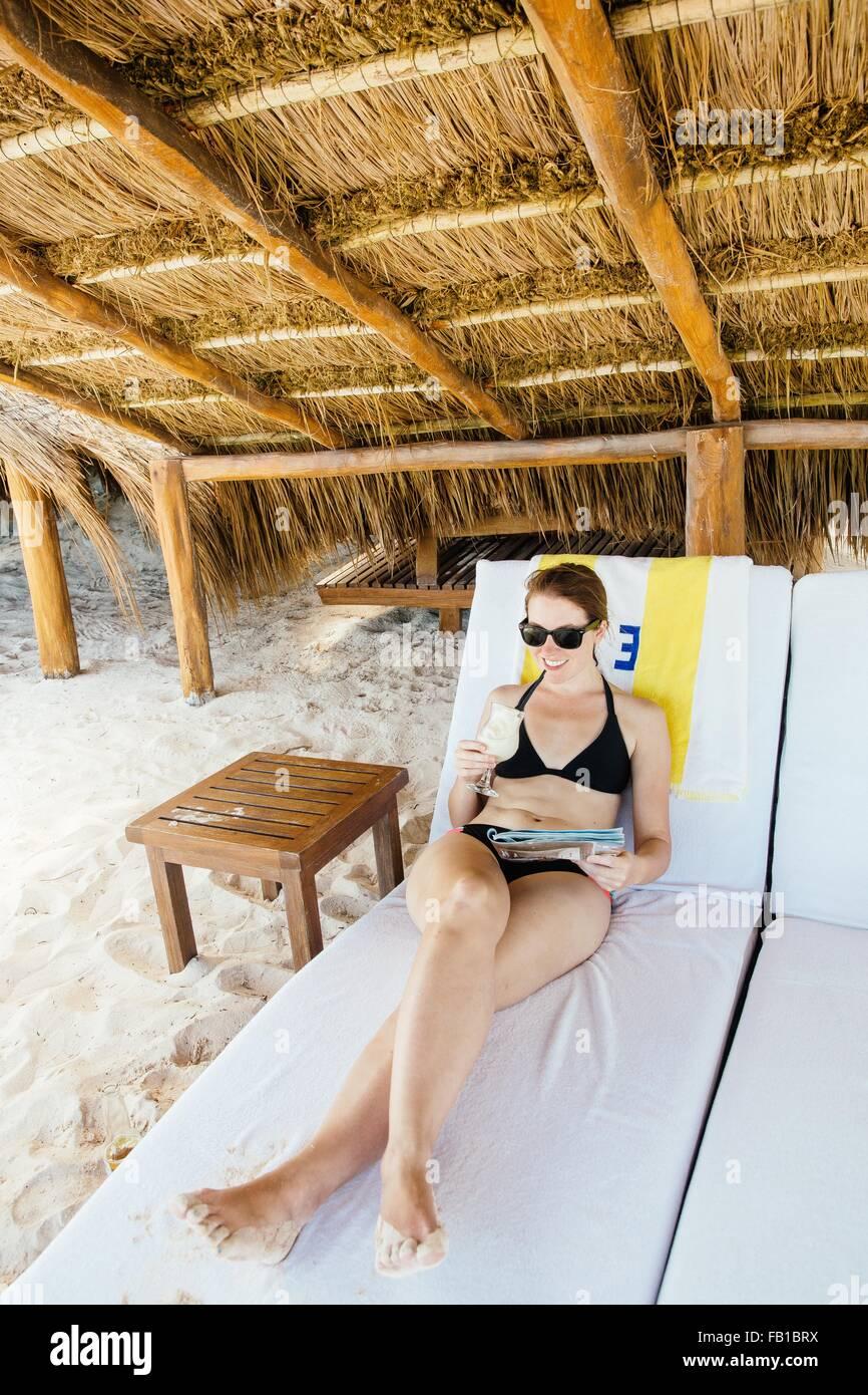 Mujer adulta media relajarse en las hamacas, bajo cabana, Tulum, Riviera Maya, México Foto de stock