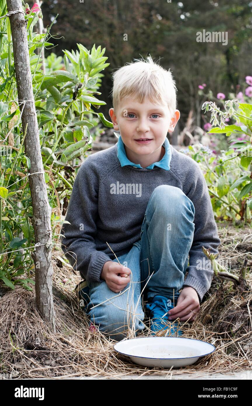 Retrato de niño arrodillado en el jardín orgánico Imagen De Stock