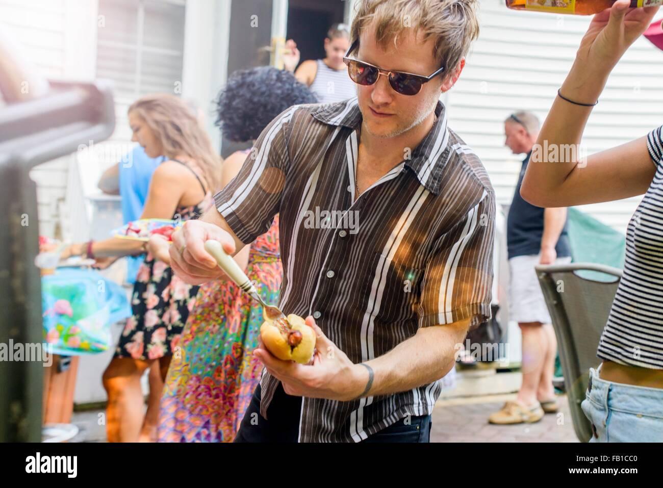 Mitad hombre adulto preparando hotdog en la barbacoa en el jardín Foto de stock