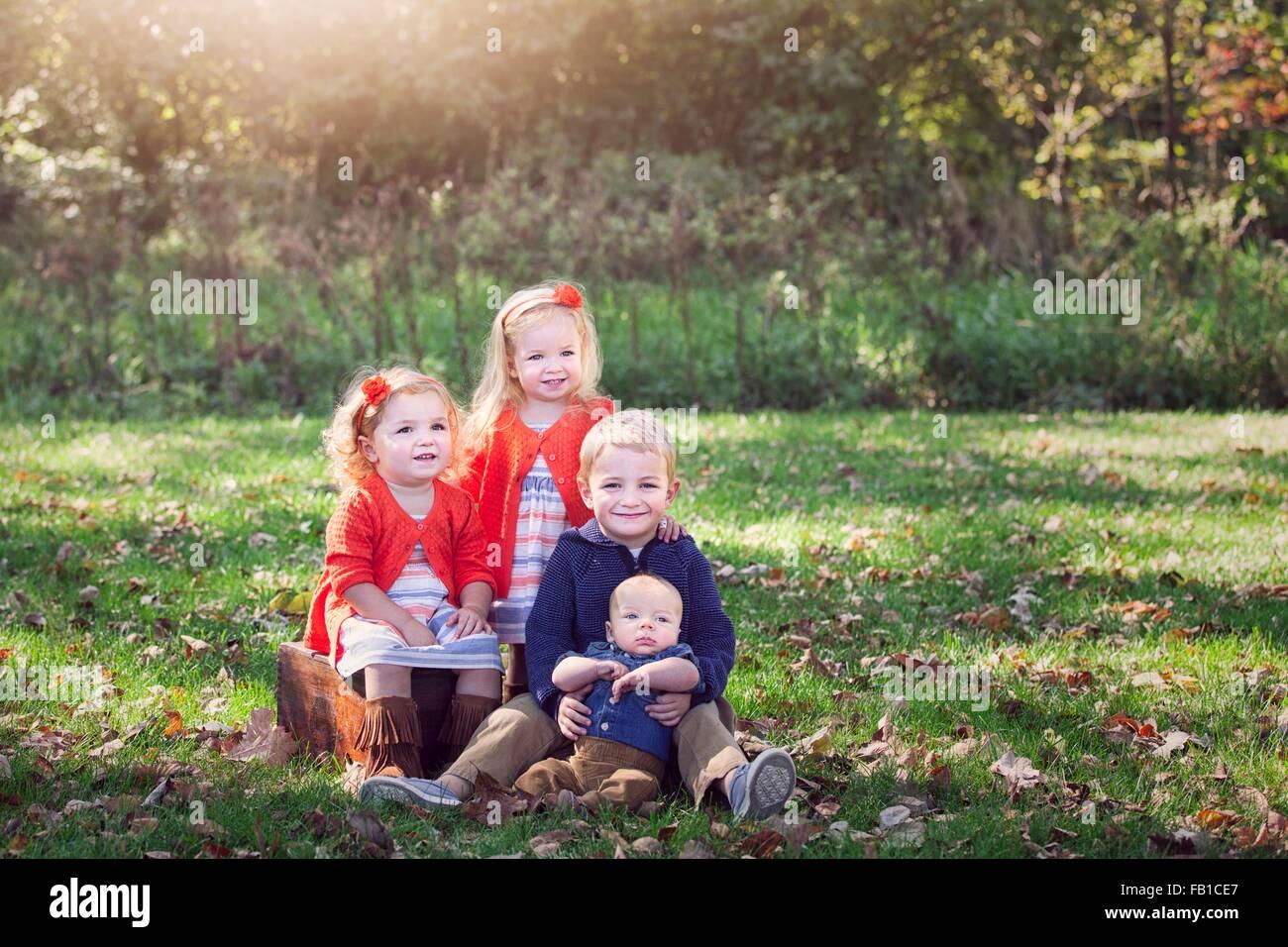 Cuatro niños de la familia de césped cubierto de hojas de otoño posando para fotografía sonriendo Imagen De Stock
