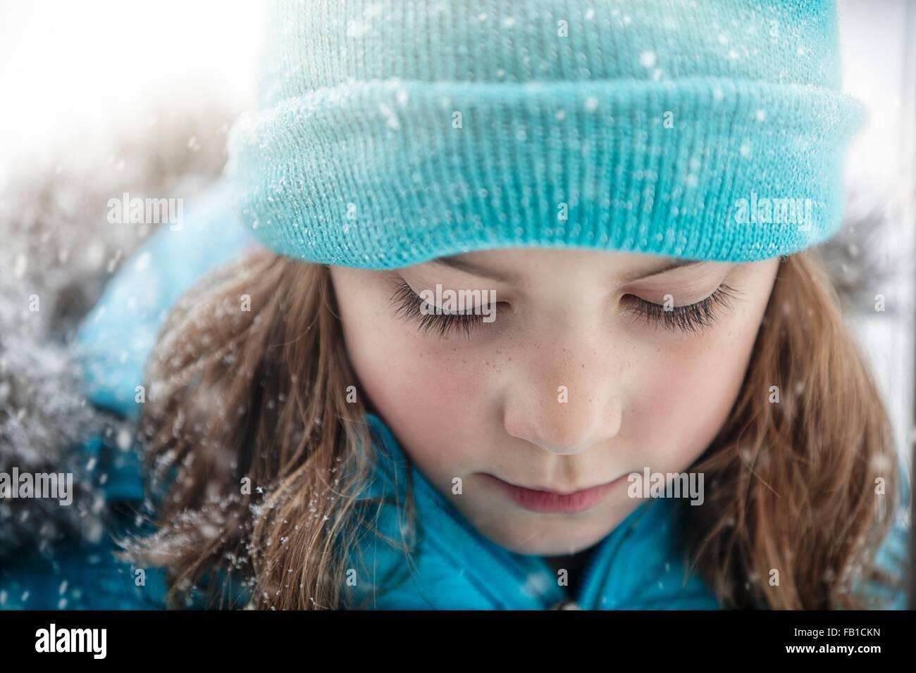 Close Up retrato de chica que llevaba knit hat mirando hacia abajo, nevando Imagen De Stock