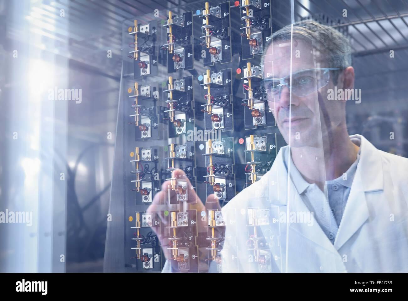 Scientist inspección de prueba en las baterías de iones de litio de la cámara de calor en las instalaciones de investigación Foto de stock