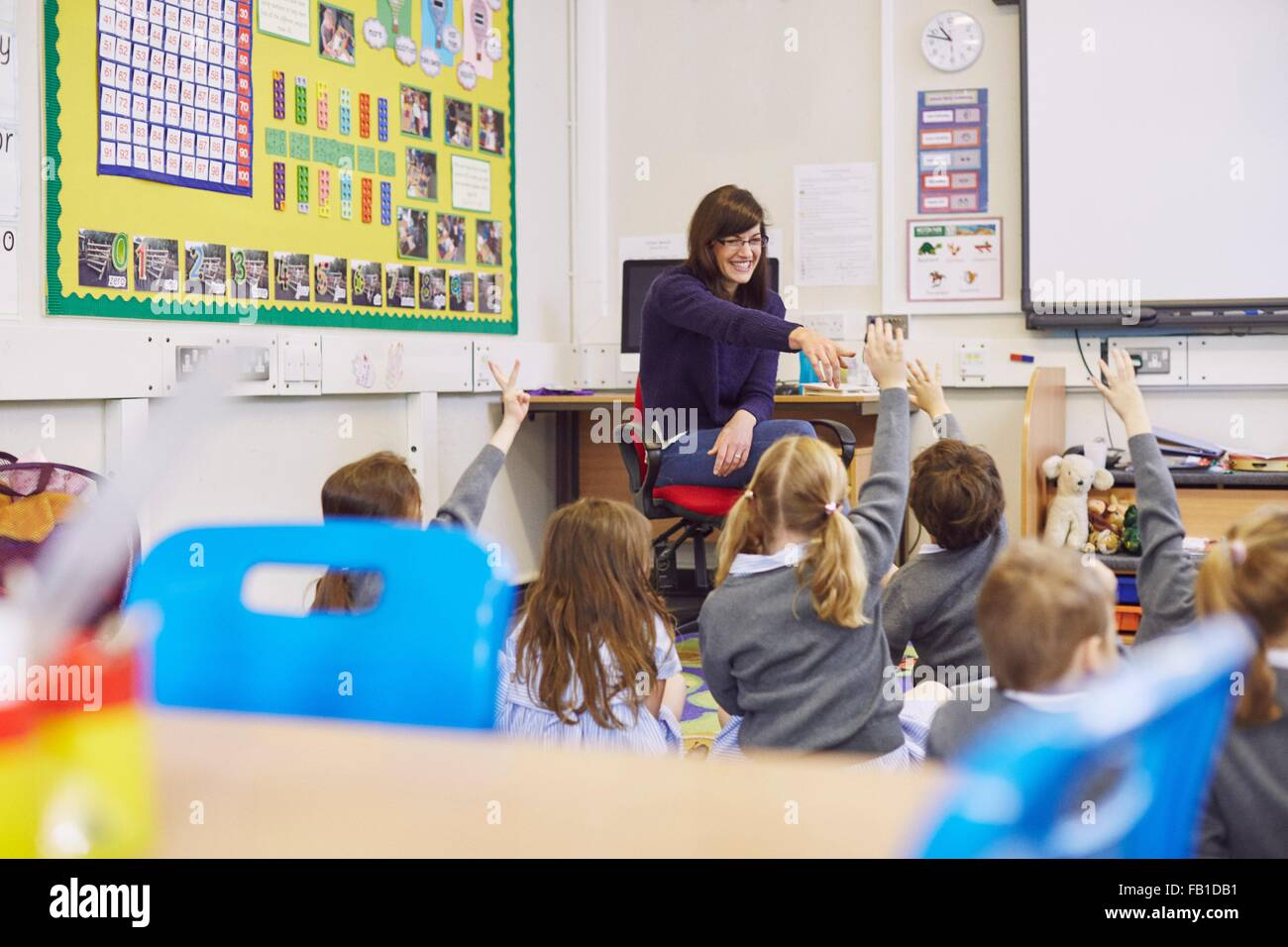Profesor cuestionando niños sentados en el suelo en las aulas de la escuela elemental Imagen De Stock
