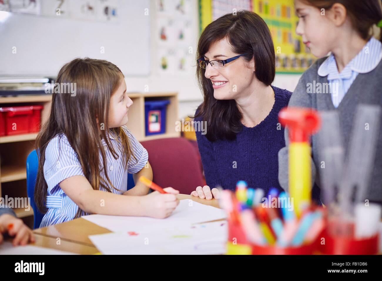 Las niñas dibujo en pupitres en las aulas de la escuela elemental Imagen De Stock